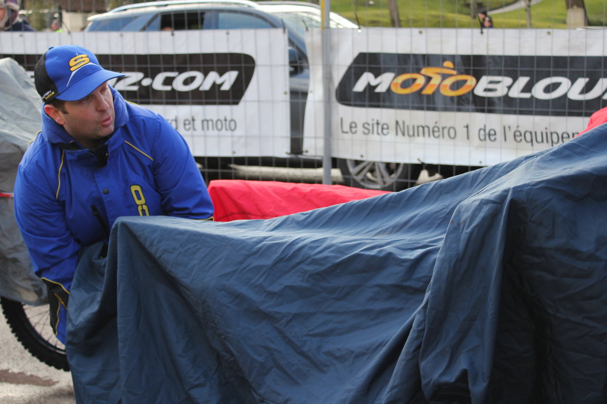 Arnaud bâche consciencieusement la Sherco avant de la laisser au parc moto