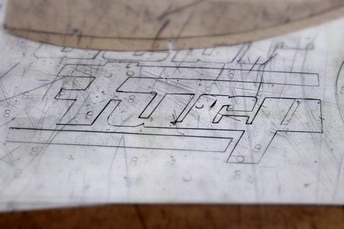 Un logo tracé à la main sur une table de couturière