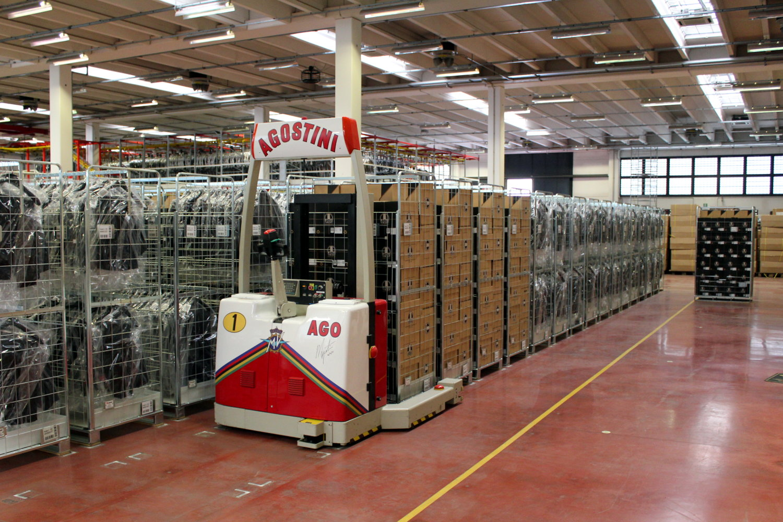 Un chariot élévateur automatisé, aux couleurs d'Agostini, déplace une cage de produit pour l'envoyer en stock
