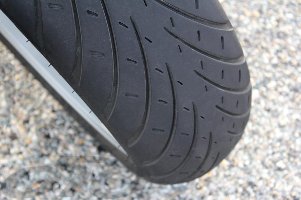 Le pneu arrière est bigomme, tandis que le pneu avant fait appel à la gomme la plus tendre qu'on retrouve sur les épaulements à l'arrière