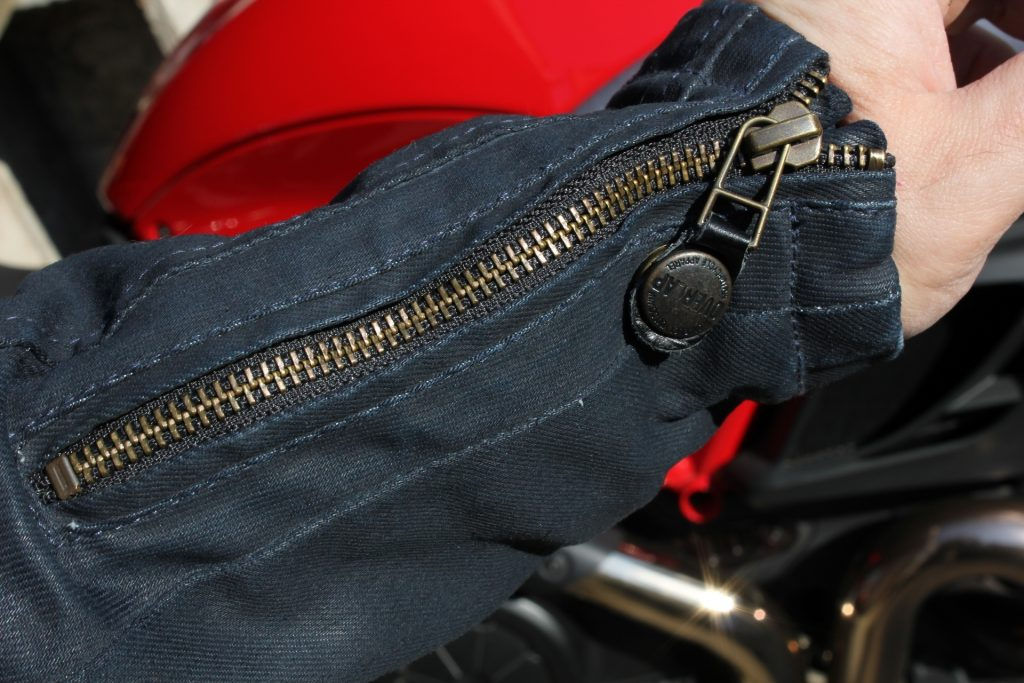 Réglage par zip en bout de manche, et l'astucieuse pression permettant de maintenir la languette