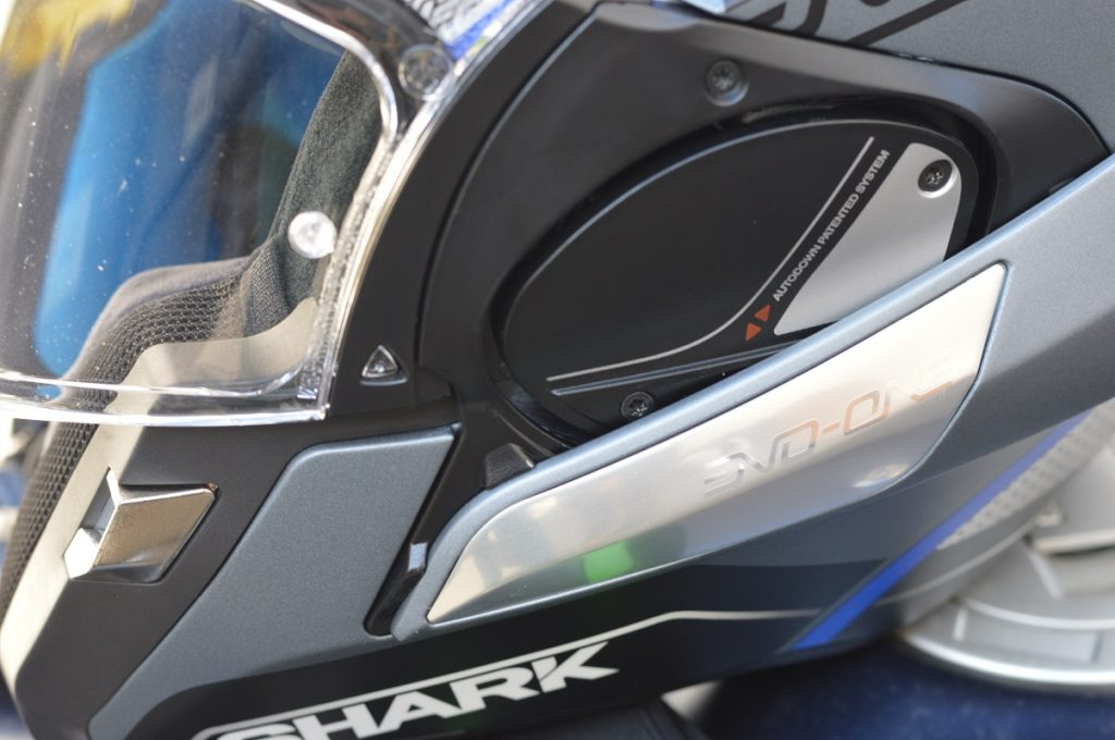 Système Auto-up et Auto-down permettant le déverrouillage simultané de l'écran et de la mentonnière lors du passage d'intégral à jet