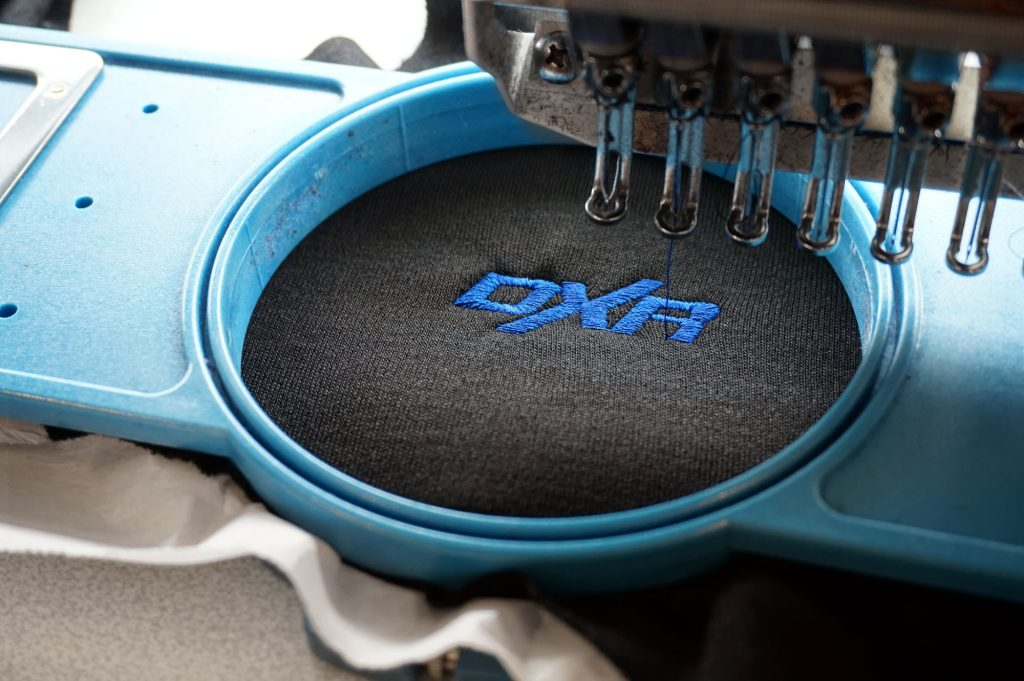 Broderie automatisée d'un logo DXR sur la poitrine d'un haut DXR Vaillant