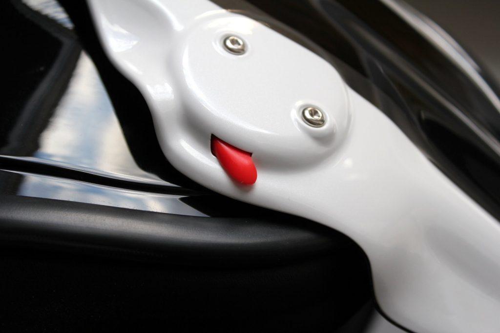 Pour les cas d'urgence, en actionnant les deux petits ergots rouge, on ouvre la mentonnière