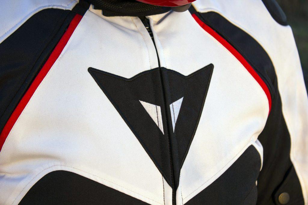 Le grand logo propre aux blousons sportifs de Dainese est présent sur le torse. Notez les deux zip d'aération et leurs liserés rouges.