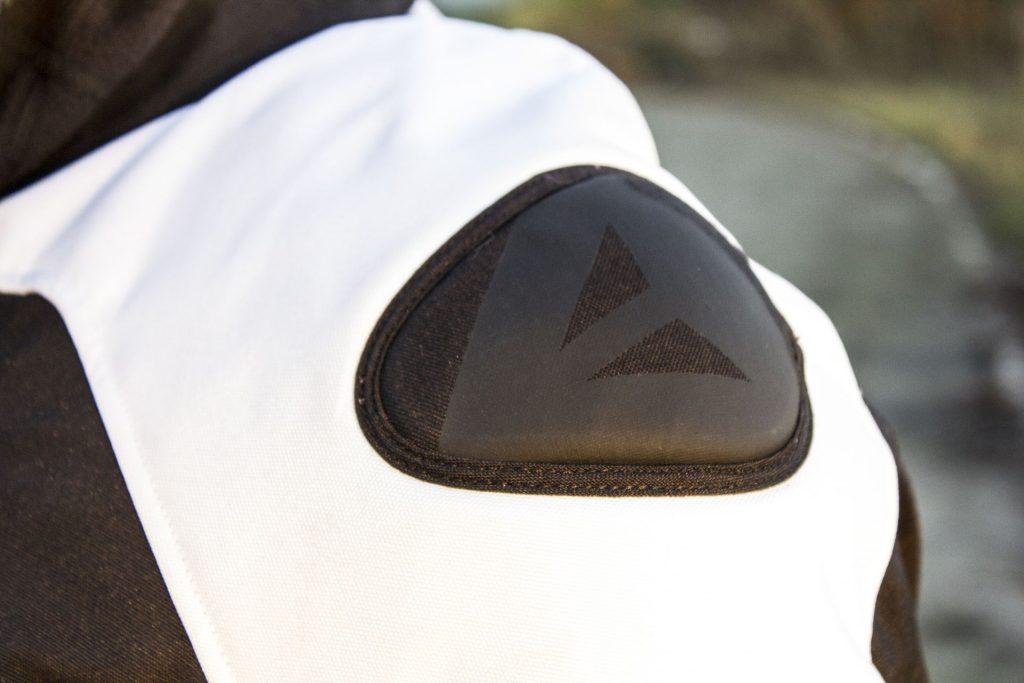 Un renfort en plastique recouvert de tissu et orné du logo Dainese qui rappelle les blousons racing de la marque