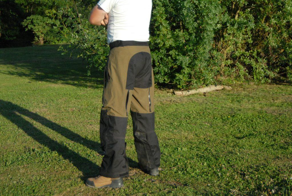 Cette vue de trois-quarts arrière permet de voir le réglage des bas de jambes par velcro du pantalon Klim Traverse