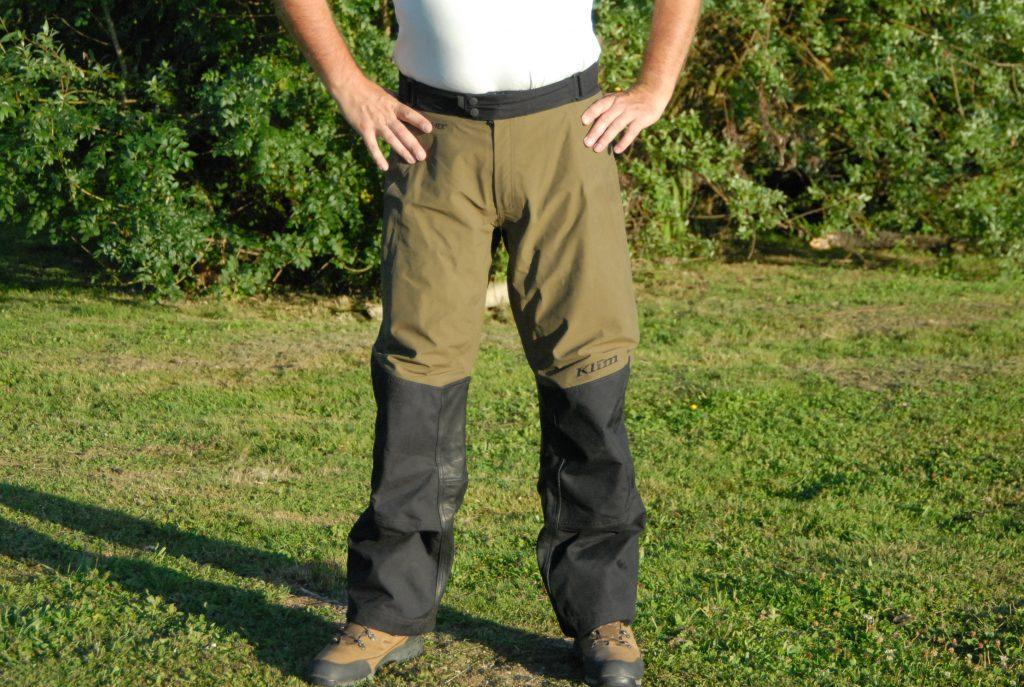 La vue de face du pantalon Klim Traverse permet de voir le grand empiècement de cuir et la coupe ample des jambes.