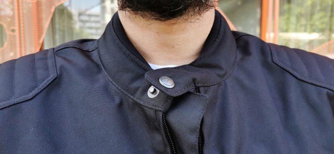 le col cerclé de néoprène avec son bouton pression pour un look néo-rétro